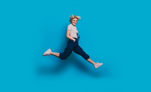 Энергичная очаровательная женщина со светлыми волосами улыбается в камеру и прыгает на синей стене студии