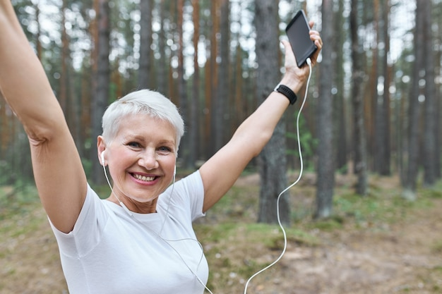 Energetic cheerful retired female with fit slim body posing outdoors in earphones, raising hands, holding cell phone