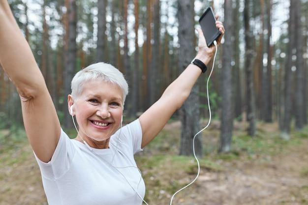 Энергичная жизнерадостная пенсионерка с подтянутым стройным телом позирует на улице в наушниках, поднимает руки и держит сотовый телефон