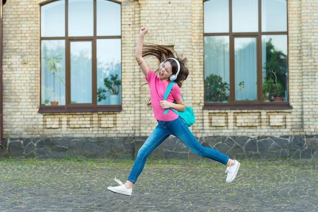 Энергичная девочка ребенка скачет, танцы наушников прослушивания музыки, концепция активной жизни.