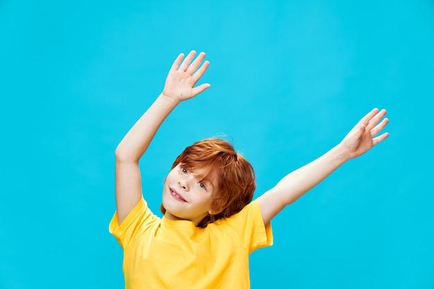 彼の手で黄色のtシャツのジェスチャーでエネルギッシュな子