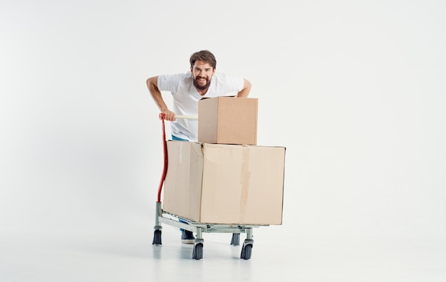 Energetic courier with cardboard boxes transporting heavy cargo light background