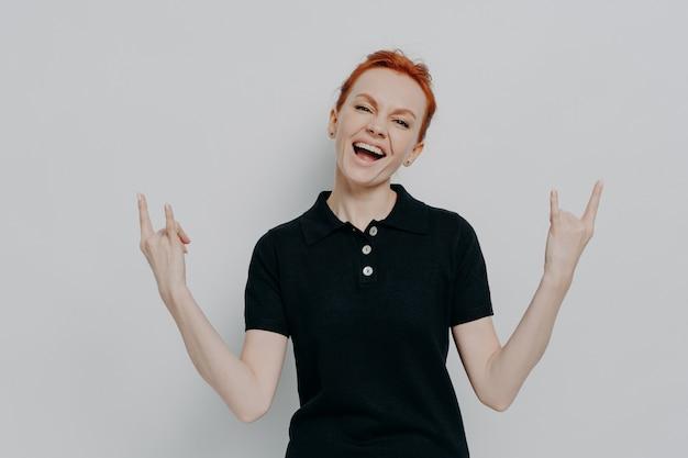 Энергичная сумасшедшая молодая женщина с рыжими волосами держится за руки в знаке рок-н-ролла и кричит