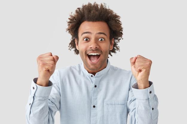 エネルギッシュな巻き毛の若い男は楽しい表情を持っている、幸せで拳を食いしばって、成功した日を祝う、エレガントな白いシャツを着て、屋内に立つ
