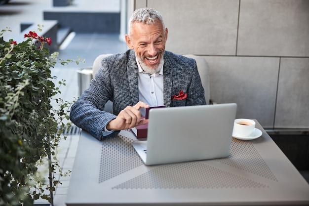 웃으면 서 컴퓨터 화면에 플라스틱 카드를 보여주는 활기찬 노인 사업가