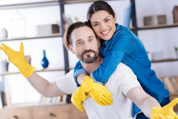 手袋をはめて妻を抱き締めながら直視する元気で熱狂的な若い夫婦