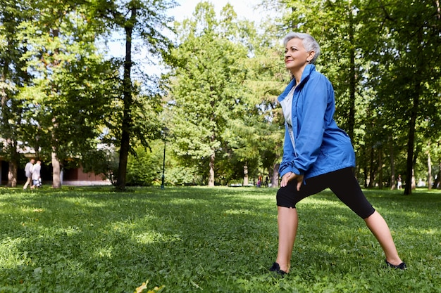 Energetic female pensioner in stylish sportswear choosing healthy active lifestyle training on green grass in forest or park, doing lunges, having happy joyful look. aged people, fitness and summer