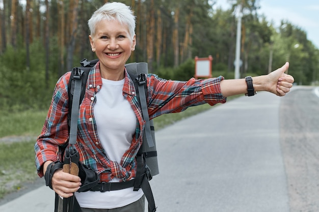 Energetic female pesnioner in active wear standing on road with rucksack behind her back hitchhiking making sign with thumbs up gesture, signaling that she needs a ride.