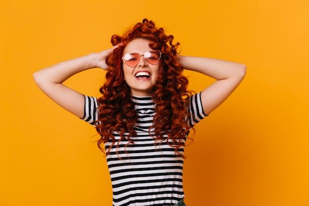 Энергичная девушка в полосатой футболке и розовых солнцезащитных очках взъерошивает вьющиеся рыжие волосы и улыбается.