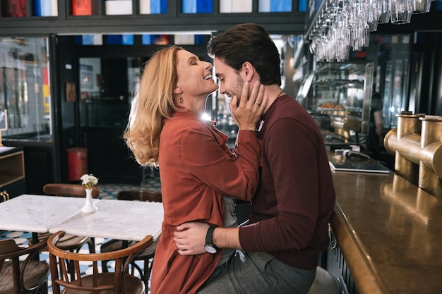 Energetic glad woman touching man and posing in profile