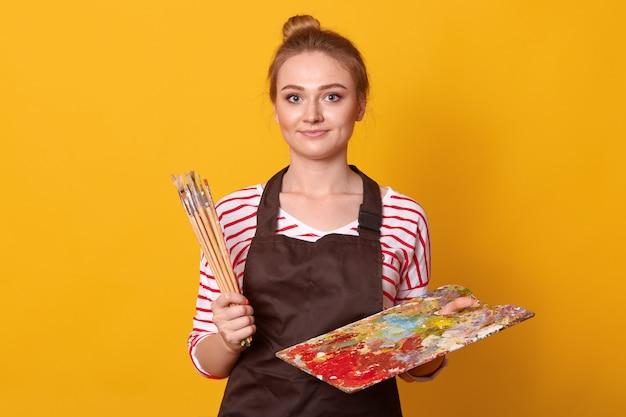 Energetic good looking amateur artist standing isolated over yellow
