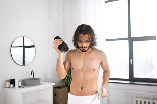 Energetic guy with white towel on hips and portable wireless bluetooth speaker dancing in bathroom
