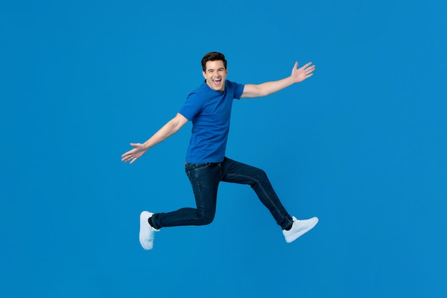 Energetic handsome man jumping and smiling with outstretched hands