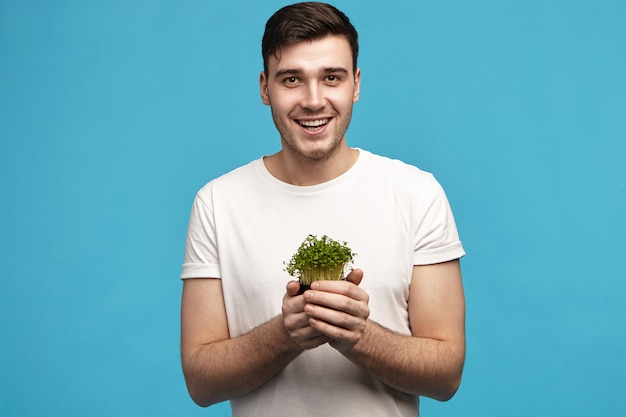 Energetic handsome young male with bristle holding micro greens in both hands