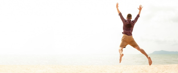 Energetic happy man jumping at the beach on summer holidays