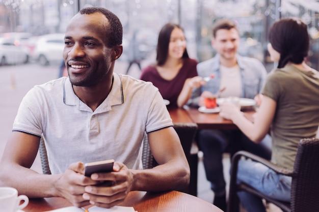 Энергичный, обнадеживающий задумчивый мужчина держит телефон, глядя в сторону и позирует в кафе