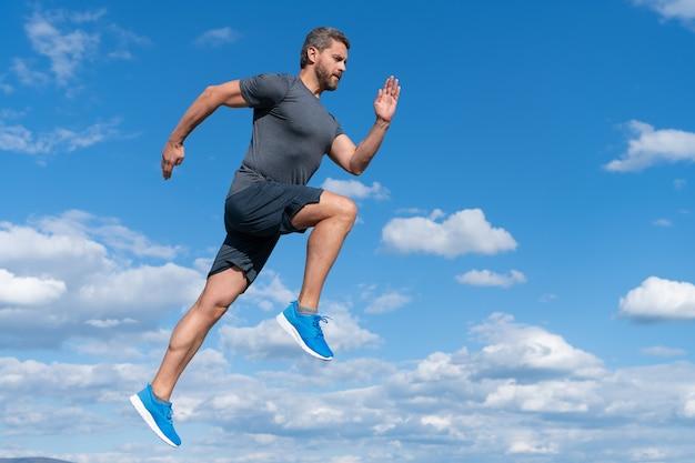 근육질의 몸을 가진 활기찬 남자 육상 선수는 하늘 배경, 동기 부여에 야외 운동복을 입고 실행합니다.
