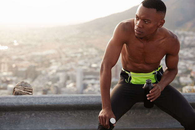 肌が黒くエネルギッシュな男性は、自信に満ちた表情を脇に置き、水でボトルを持ち、岩の多い地形でポーズをとり、筋肉のあるスポーティな体をしています。フィットネス、レクリエーション、ライフスタイルのコンセプト