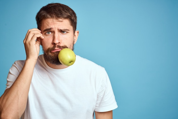 An energetic man with a green apple on a blue background gestures with his hands copy space emotions. high quality photo