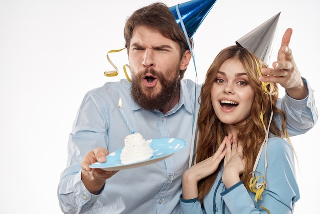 Energetic man and woman with a cake and in hats celebrate a birthday on a light wall.
