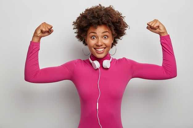 Energetic powerful afro american lady raises arms to show muscles and strength, smiles broadly, wears stereo headphones around neck
