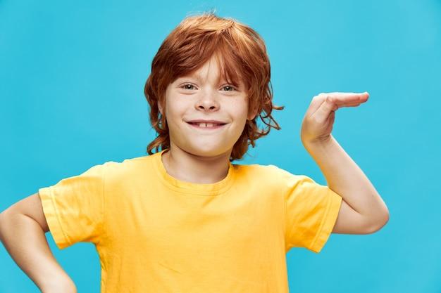 Энергичный ребенок с красными волосами танцует на синем фоне африканский танец желтая футболка