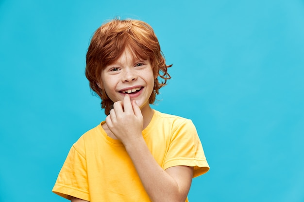黄色のtシャツで分離されて笑っているエネルギッシュな赤い髪の子