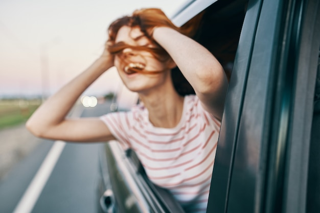 Energetic redhaired tshirt woman peeking out of the open car window on the road track journey