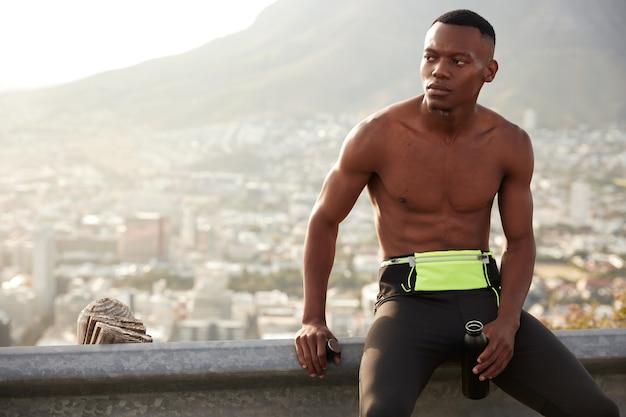 활기찬 shirtless 어두운 피부를 가진 남자는 근육, 짧은 헤어 스타일, 도로 표지판에 기대고 피곤하고 목이 마르고 병을 들고 있습니다. 수분 공급, 피로감 및 운동 개념