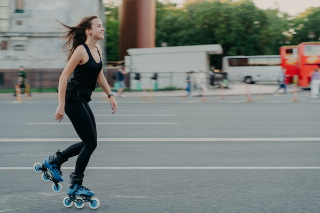 Energetic slim young smiling woman rollerblades on city road enjoys spending free time actively moves quickly has dark hair floating on wind leads healthy lifestyle. active weekends. outdoor photo