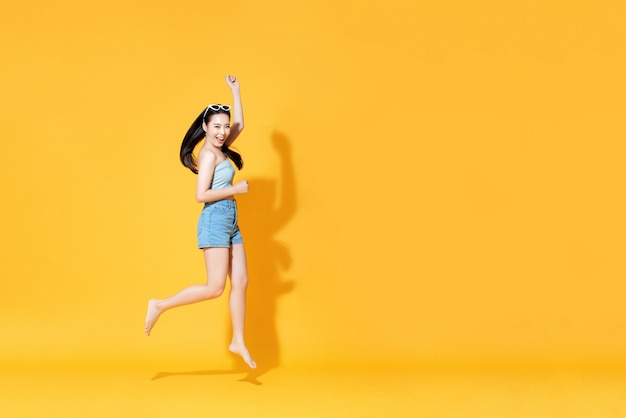 Energetic smiling beautiful asian woman in summer outfit jumping