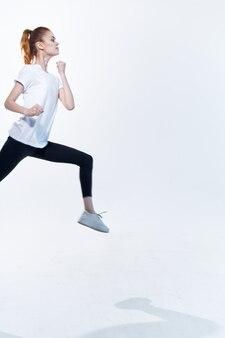 エネルギッシュなスポーティーな女性ジャンプトレーニングフィットネス