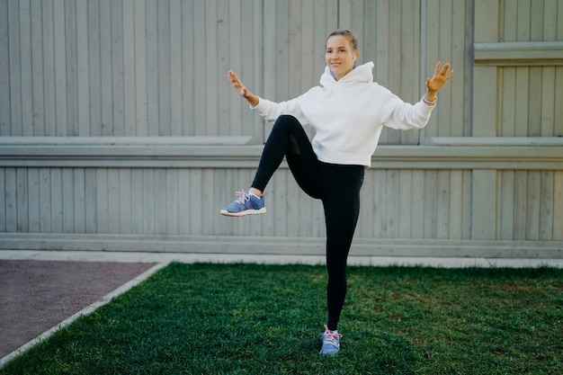 Energetic sportwoman has workout routine poses on one legs demonstrates her stamina warms up before jogging dressed in hoodie leggings and trainers trains outdoors. sport and motivation concept