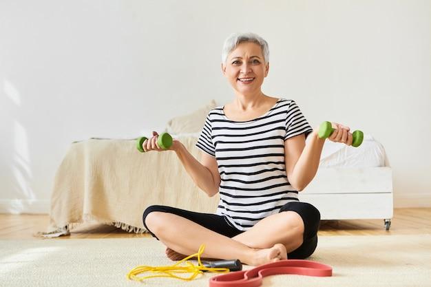 自宅で健康的なアクティブライフスタイルトレーニングを選択し、ダンベルを持って床に座り、スポーツ用品を使用して運動を行うエネルギッシュなスポーティな女性年金受給者。フィットネス、体型、健康