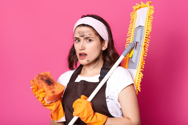 Energetic surprised slender model holds broom on her shoulder, ready to continue general cleaning with dirty bright sponge in her hand, looks exhausted and shocked. household cleaning concept.