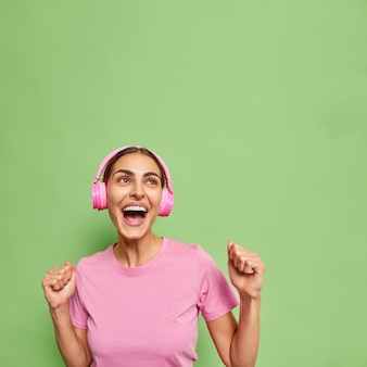 Energetic upbeat young woman in casual t shirt dances carefree clenches fists sings song along wears wireless headphones isolated over green wall enjoys fantastic sound feels very happy