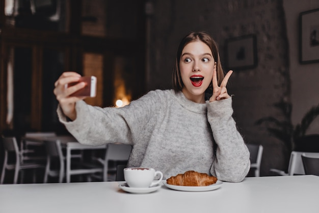 Energetic woman in gray sweater and red lipstick makes selfie. portrait of girl showing peace sign in cafe with croissant on table.