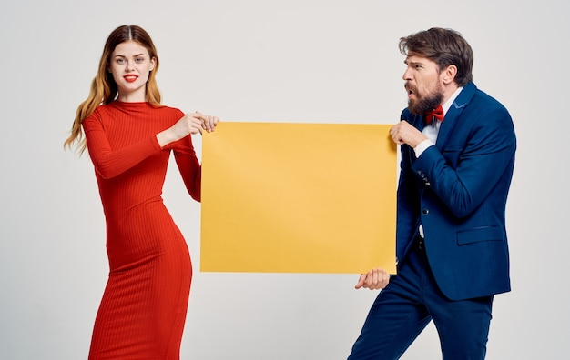 Energetic woman takes the mockup poster from the hands of a man advertising model