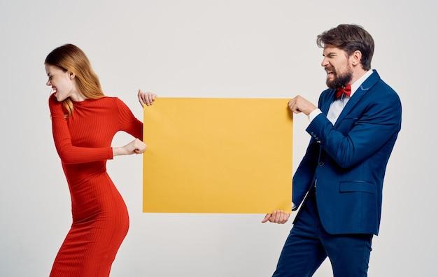 활기찬 여자는 남자 광고 모델의 손에서 모형 포스터를 가져옵니다