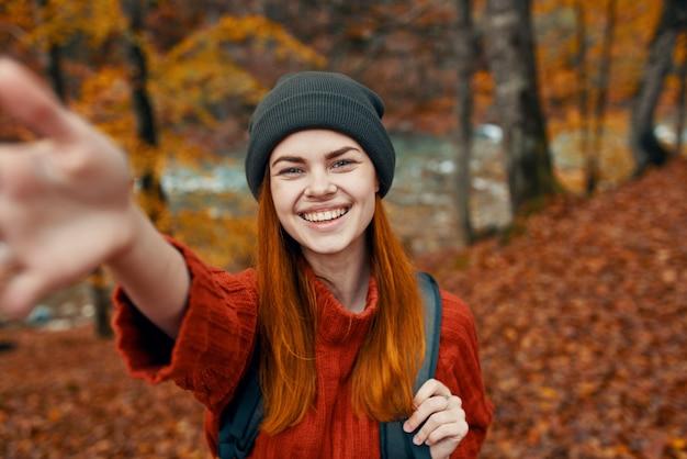 Энергичная туристка с рюкзаком в красном свитере и кепках отдыхает в осеннем лесу