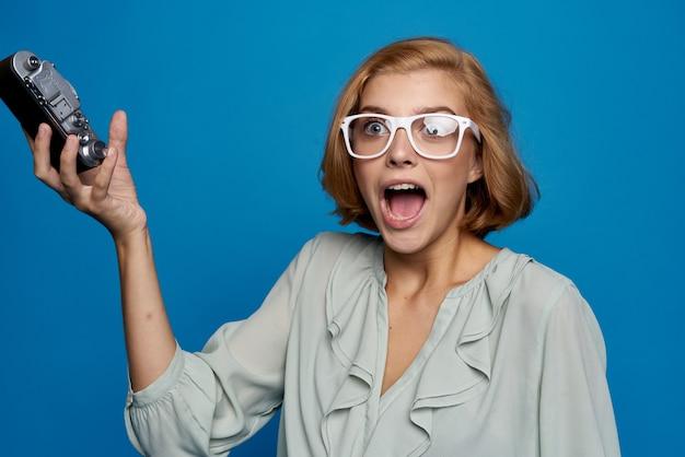 青色の背景にカメラを開いてエネルギッシュな女性が口を大きく開けて驚いた表情