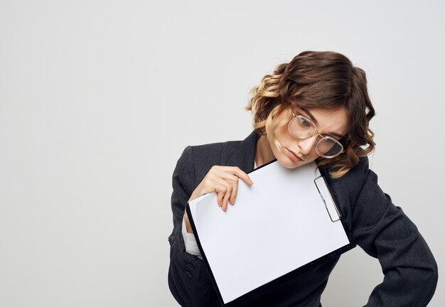 Энергичная женщина с документами в папке классический костюм свет