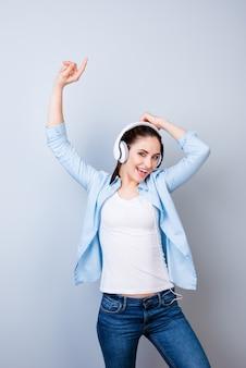 헤드폰과 춤에서 음악을 듣고 활기찬 어린 소녀