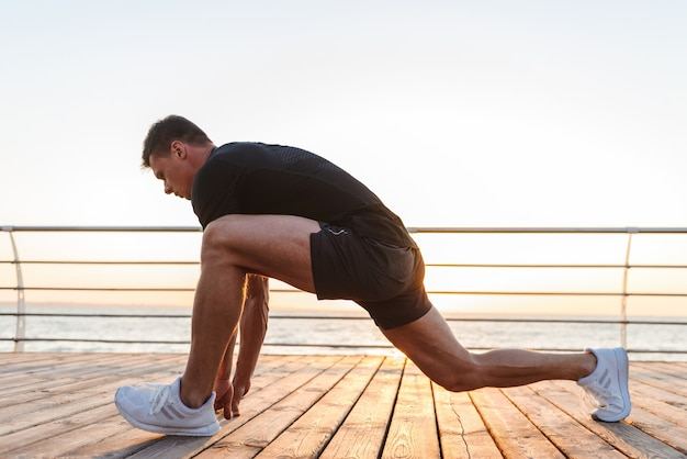 Energetic young sportsman doing stretching