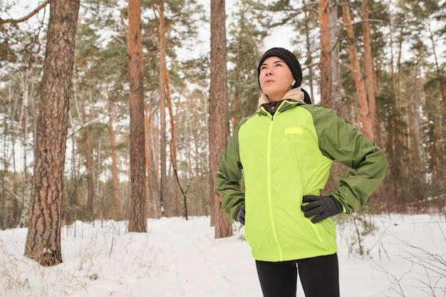 一人でハイキングしながら腰に手をつないで、森の中で凍るような空気を吸い込む緑のジャケットを着たエネルギッシュな若い女性