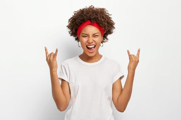 エネルギッシュな若い女性はロックンロールのジェスチャーをし、クールな音楽を楽しんで、笑顔を笑い、カジュアルな服を着ています