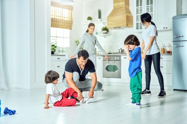 あなたの一日を活気づけます。家で朝の家族のトレーニングの準備をしている間、彼の幼い息子に靴を履いている愛情のあるヒスパニック系の父。健康的な生活様式