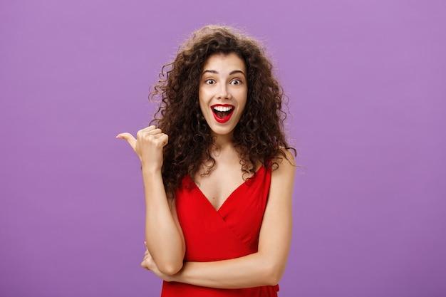 곱슬머리 헤어스타일을 하고 있는 활기차고 매력적인 여성은 놀라서 웃고, 보라색 벽 위에 빨간 드레스를 입은 흥미로운 전시에 대해 질문하는 엄지손가락으로 왼쪽을 가리키며 놀랐습니다.