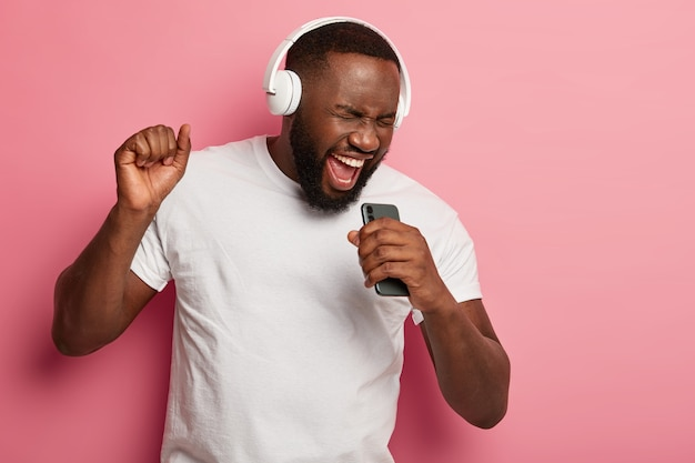 Energized black unshaven man sings to music, moves actively, wears headphones and casual t shirt, poses against pink background, keeps mouth widely opened