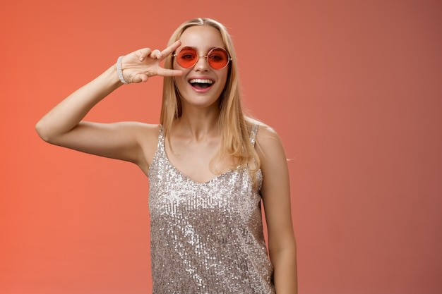 은색 세련된 드레스 선글라스에 활력을 불어 넣은 친절하고 잘 생긴 금발 25 대 여성이 평화 승리 제스처 평온한 미소 카메라를 보여 멋진 파티를 즐기고 빨간색 배경에 서 있습니다.